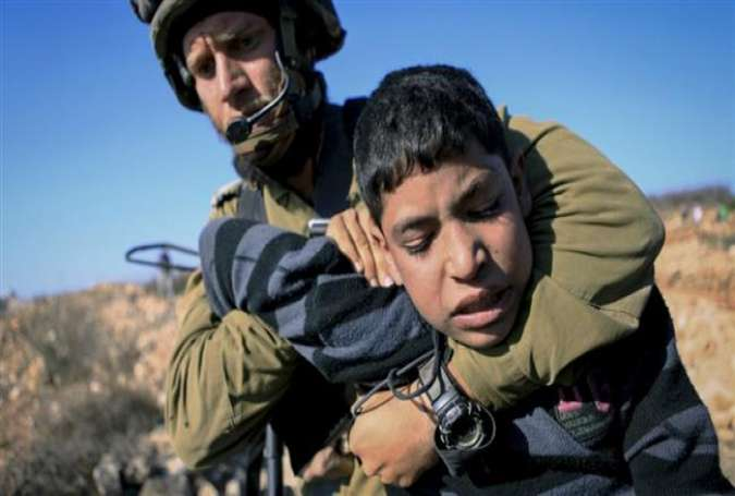 An Israeli soldier arrests a Palestinian child during a protest against the Israeli occupation and settlements in the West Bank.