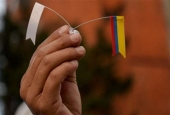 A Colombian protester holds the national flag and a white flag symbolizing peace during a march for peace in Bogota, on November 15, 2016.