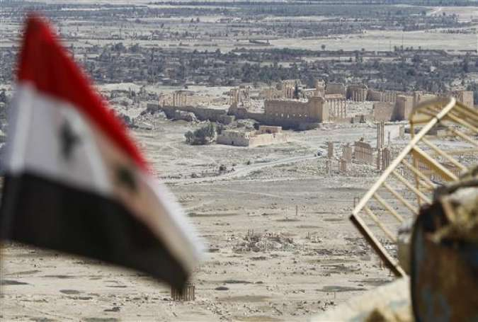 A Syrian national flag flutters as the ruins of the historic city of Palmyra are seen in the background, in Homs Governorate, Syria, April 1, 2016.