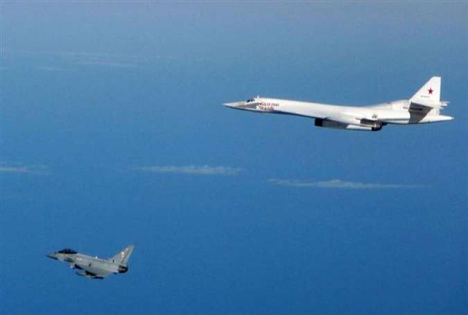 This file photo shows a Russian Tu-160 Blackjack bomber (top) escorted by RAF typhoons in September 2015.