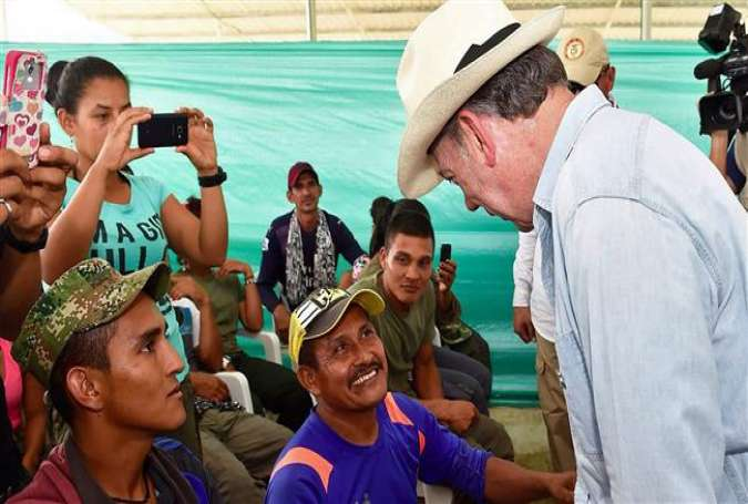 Handout photo released by the Colombian Presidency's press office shows President Juan Manuel Santos (R) meeting FARC-EP leftist guerrillas during his visit to a transition zone in La Carmelita, Puerto Asis municipality, Putumayo department, February 20, 2017.