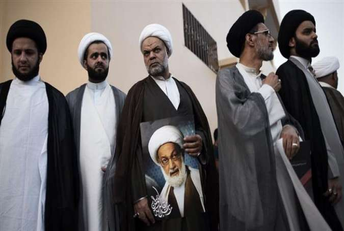Bahraini Shia clerics attend a protest against the revocation of the citizenship of senior Bahraini Shia cleric Sheikh Isa Qassim (portrait), on June 20, 2016 near his house in the village of Diraz, west of Manama.