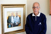 This file photo, taken on July 16, 2012, shows 82-year-old Ahmed Kathrada, an anti-apartheid activist and a close friend of former South African president Nelson Mandela, posing next to a picture of himself with Nelson Mandela in his house in Johannesburg. (By AFP)