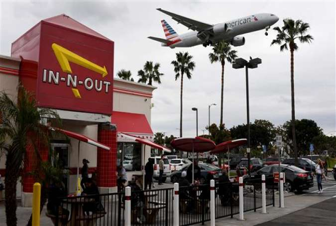 An American Airlines plane flies over a fast food restaurant as it prepares to land at Los Angeles International Airport in Los Angeles, California on March 21, 2017. (Photo by AFP)