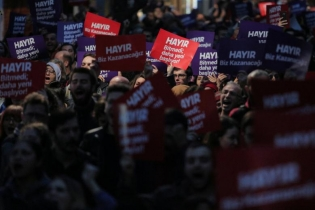 "Anti-government demonstrators shout slogans during a protest in the Kadikoy district of Istanbul, Turkey. The placards reads: ""No, we will win"" and ""Not finished, just started""."