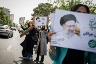 Supporters of Iranian presidential candidate Ebrahim Raisi hold his posters outside the Mosalla mosque in Tehran, Iran, May 16, 2017.