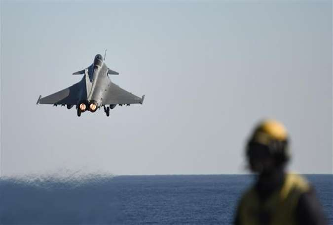 A French Rafale fighter jet takes off from the deck of France