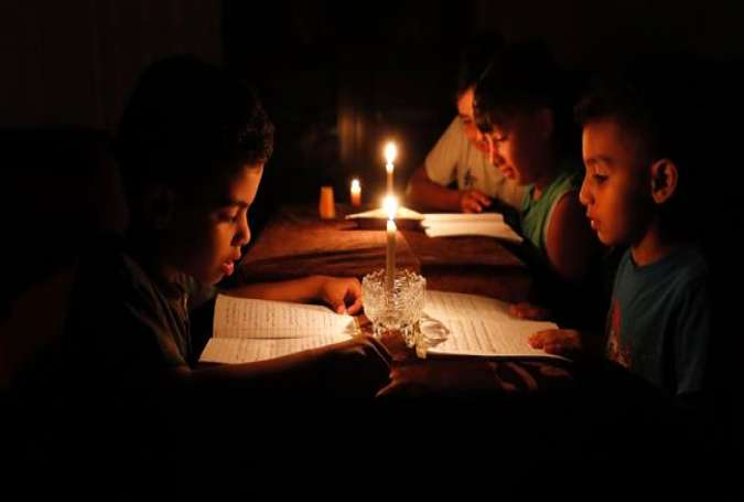A picture taken on June 13, 2017 shows Palestinian children at home reading books by candle light due to electricity shortages in Gaza City. (By AFP)