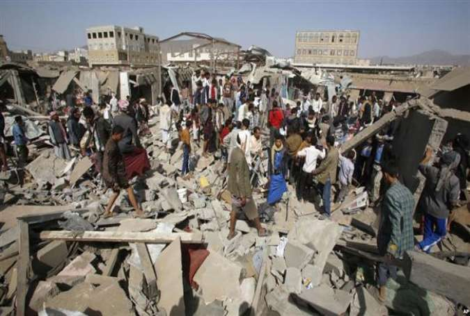People gather on the rubble of shops destroyed in a Saudi airstrike at a market in Sana