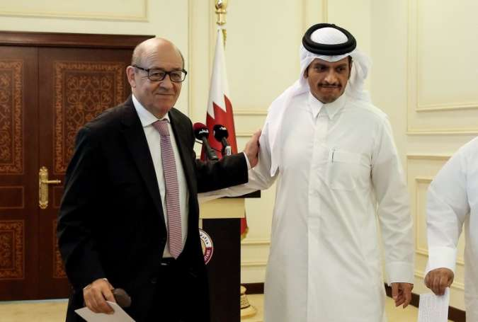 French Foreign Minister Jean-Yves Le Drian (L) and his Qatari counterpart Mohammed bin Abdulrahman al-Thani in Doha