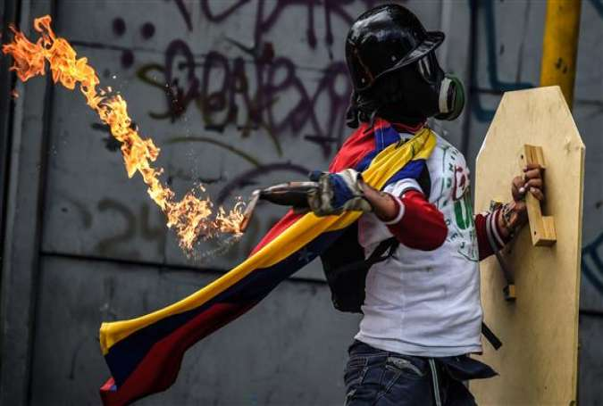 This image shows a protester about to throw a Molotov petrol bomb at police during a march toward the Supreme Court, in Caracas, Venezuela, July 22, 2017. (By AFP)
