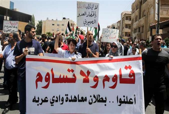 "Jordanian protesters hold a banner reading in Arabic ""resist and do not compromise, declare the annulment of the Wadi Araba [peace] treaty"" with Israel, during a demonstration near the Israeli embassy in Amman on July 28, 2017. (Photo by AFP)"