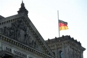 The German flag flutters at half-mast on the Reichstag building housing the Bundestag (lower house of parliament) in Berlin, where is being held an hour of commemoration on January 27, 2017, the International Holocaust Remembrance Day. (Photo by AFP)
