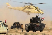An Iraqi military helicopter flies above the vehicles of the Popular Mobilization Units during an operation in Iraq, March 2, 2016. (Photos by AFP)