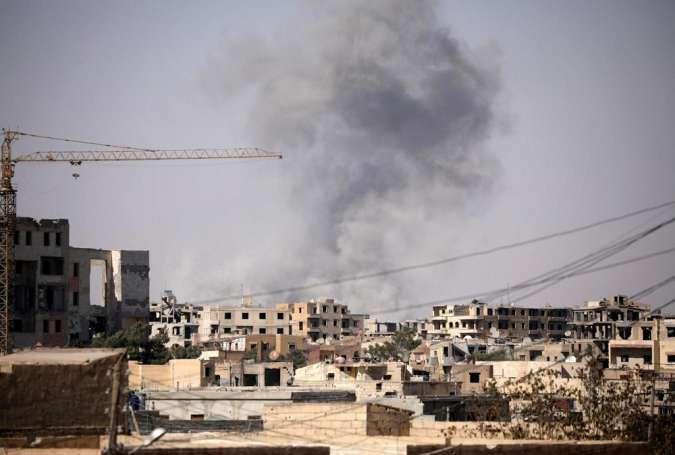 Smoke rises from a building in Raqqa, Syria