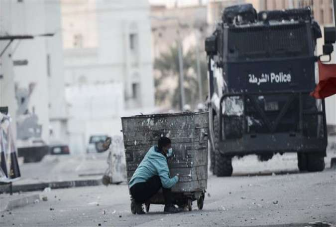 This AFP file photo taken on January 2, 2015 shows a Bahraini protester taking cover behind a garbage container during clashes with riot police following a demonstration on January 2, 2015.