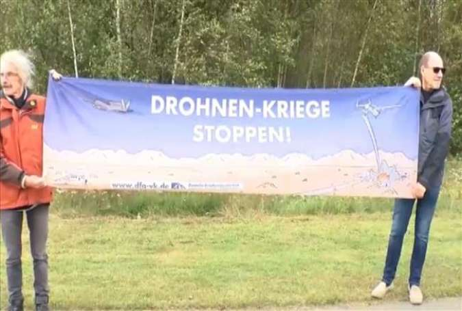 This video grab shows two demonstrators holding a placard during a protest against warmongering, in Ramstein-Miesenbach municipality, Germany, on September 9, 2017.