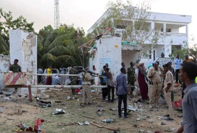 People stands outside the scene of an attack on a hotel and an adjacent restaurant in Mogadishu, Somalia