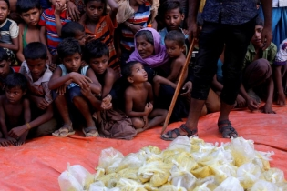 Rohingya refugees wait for the food to be distributed by local organisation outside a mosque in Cox