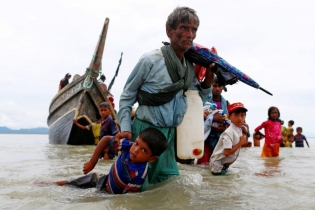 A Rohingya refugee man pulls a child as they walk to the shore after crossing the Bangladesh-Myanmar border by boat through the Bay of Bengal in Shah Porir Dwip, Bangladesh.
