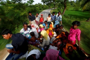 Rohingya refugees travel on a truck to Kutupalang makeshift refugee camp in Cox