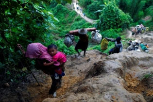 Rohingya refugees climb up a hill after crossing the Bangladesh-Myanmar border in Cox