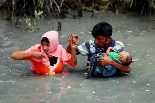 Rohingya refugees carry their child as they walk through water after crossing border by boat through the Naf River in Teknaf, Bangladesh.
