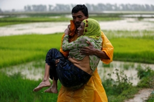 A local man carries an old Rohingya refugee woman as she is unable to walk after crossing the border, in Teknaf, Bangladesh.
