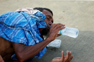 A Rohingya refugee man drinks water after crossing the Bangladesh-Myanmar border by boat through the Bay of Bengal in Teknaf, Bangladesh.
