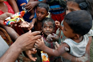 Rohingya refugees stretch their hands for food after crossing the Bangladesh-Myanmar border, in Teknaf, Bangladesh.