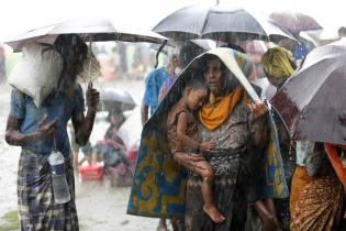 Rohingya refugees stands in an open place during heavy rain, as they are hold by Border Guard Bangladesh (BGB) after illegally crossing the border, in Teknaf, Bangladesh.