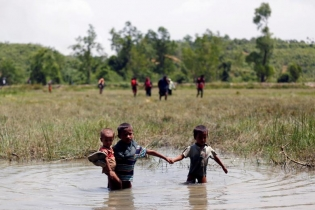 Rohingya children make their way through water as they try to come to the Bangladesh side from No Man�s Land after a gunshot being heard on the Myanmar side, in Cox