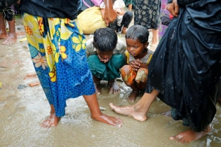 Children among Rohingya refugee people sit on the mud during heavy rain, as they are hold by Border Guard Bangladesh (BGB) after illegally crossing the border, in Teknaf, Bangladesh.