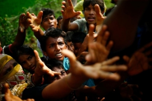 Rohingya refugees stretch their hands for food near Balukhali in Cox