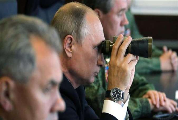 Russian President Vladimir Putin (c) uses a pair of binoculars as he inspects the joint Zapad-2017 (West-2017) Russian military exercises with Belarus at the Luzhsky training ground in Leningrad region on September 18, 2017. (Photo by AFP)