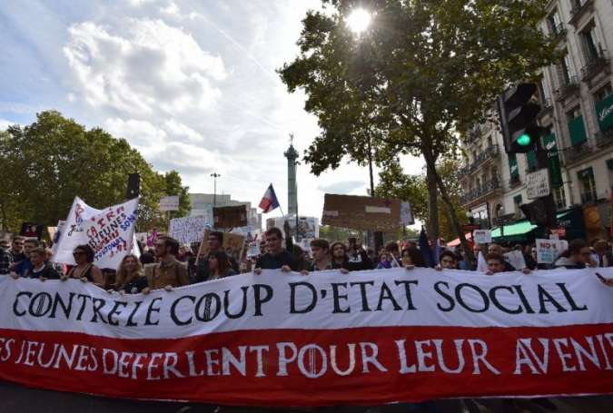 "Demonstrators hold a banner reading, ""Against the social coup d'état"" during a protest over the president's labour reforms in Paris"