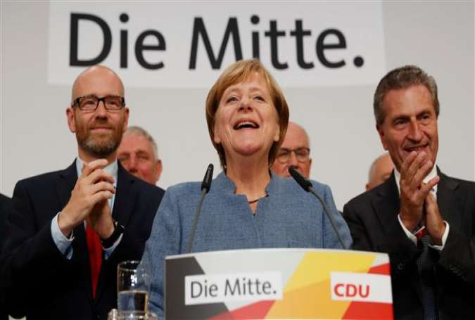 German chancellor and CDU party leader, Angela Merkel (C), addresses supporters after exit poll results were broadcasted on public television at an election night event at the party