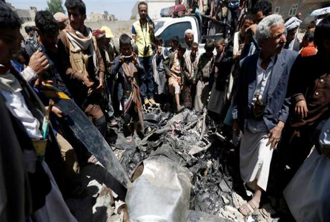 People gather around the engine of an unmanned aerial vehicle, which Houthi Ansarullah fighters said they downed in Sana'a, Yemen, on October 1, 2017. (Photo by Reuters)