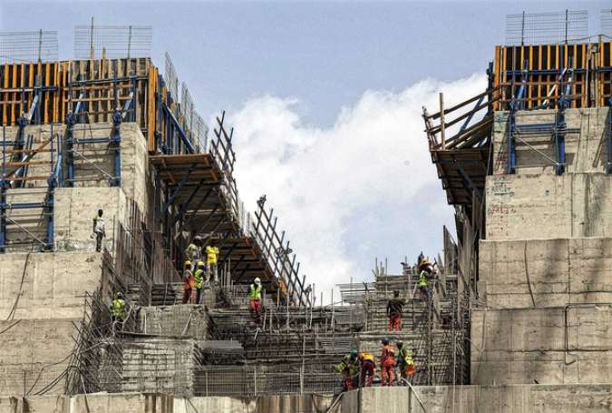 Workers stand on scaffolding during the construction of the Grand Renaissance Dam near the Sudanese-Ethiopian border, March 31, 2015. (Photo by AFP/Getty Images)