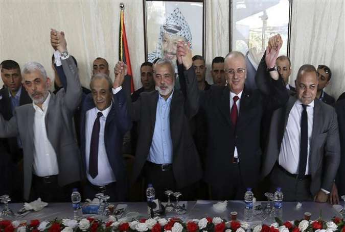 Fatah and Hamas officials hold their hands up during a meeting in Gaza City, October 2, 2017. (Photo by AP)