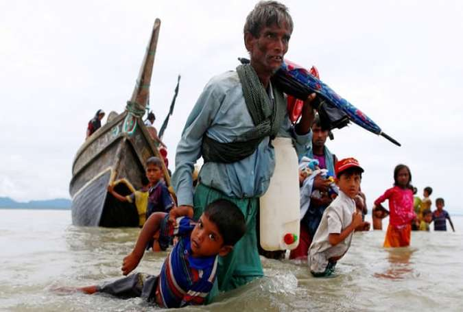 A Rohingya refugee pulls a child as they flee toward the shore after crossing the Bangladesh-Myanmar border by boat