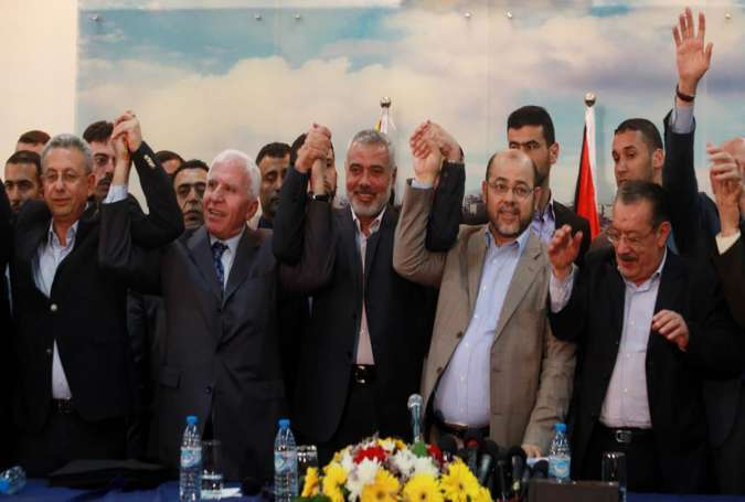 Palestinian officials of rival Hamas and Fatah parties hold hands in a sign of national unity in Cairo, Egypt, in this photo released by Palestinian media on October 12, 2017.