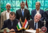 Head of Hamas delegation Saleh Arouri (left) and Fatah leader Azzam al-Ahmad (right) sign a reconciliation deal in Cairo