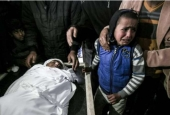 Palestinian children mourn next to the body of 18-year-old Youssef Abou Azra during his funeral in Rafah in the southern Gaza Strip on March 22, 2017.