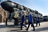 This file photo shows military specialists walking past a Russian Topol intercontinental ballistic missile (ICBM) at the exposition field in Kubinka Patriot Park, outside Moscow, on August 22, 2017. (By AFP)