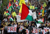 Hezbollah supporters wave the Lebanese resistance movement's flags and Palestine at anti-US rally in Beirut.jpg