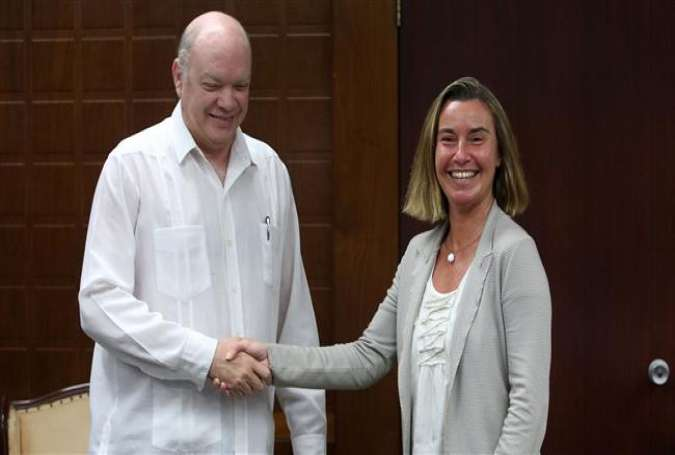 The European Union (EU)'s foreign policy director, Federica Mogherini (R), and Cuban Foreign Trade and Investment Minister Rodrigo Malmierca smile as they shakes hands during a meeting in Havana, Cuba, on January 3, 2018. (Photo by AFP)