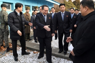 Head of North Korean delegation Ri Son Gwon, Chairman of the Committee for the Peaceful Reunification of the Country (CPRC) of DPRK, reaches out to shake hands with a South Korean official as he crosses a concrete border to attend their meeting at the tr