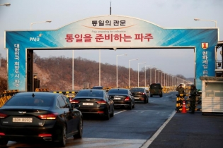 Vehicles transporting the South Korean delegation led by Cho Myoung-gyon, Minister of South Korean Unification Ministry, drive past a checkpoint on the Grand Unification Bridge that leads to the truce village of Panmunjom, just south of the demilitarized