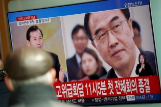 A man watches a TV broadcasting a news report on a high-level talks between the two Koreas at the truce village of Panmunjom, in Seoul, South Korea.